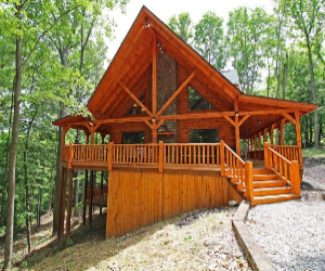 two story log cabin with tall green trees and large wrap around deck