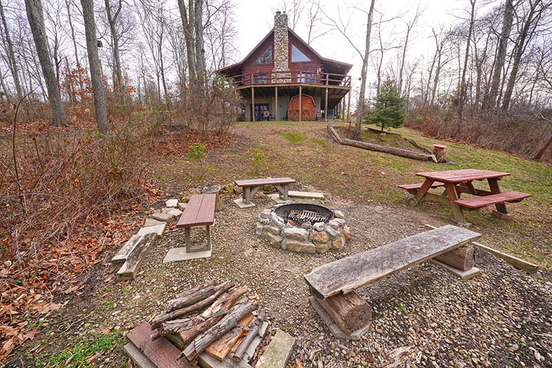 firepit with seating, cabin in background