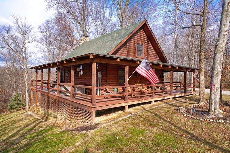 side view of cabin, american flag, stones around tree
