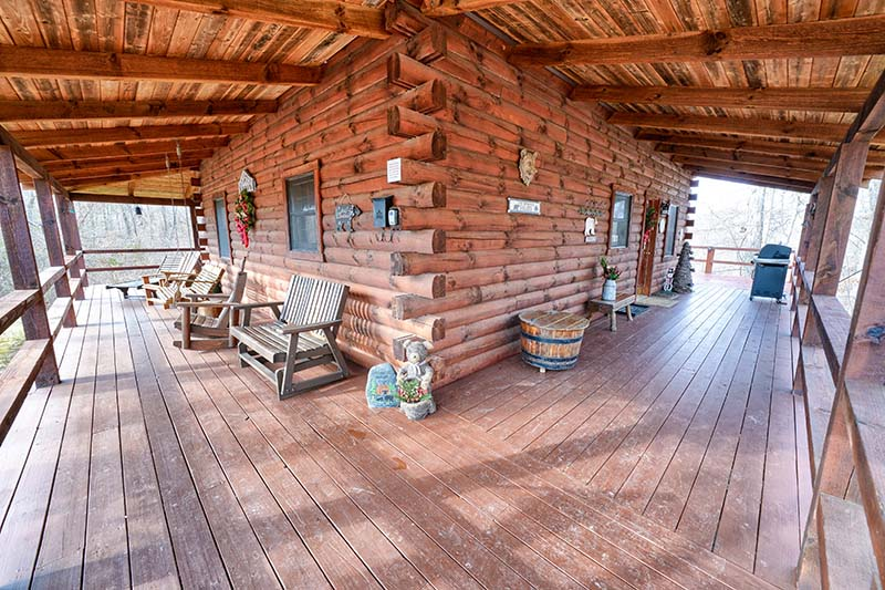 log view of corner of cabin, outdoor seating on wrapped porch