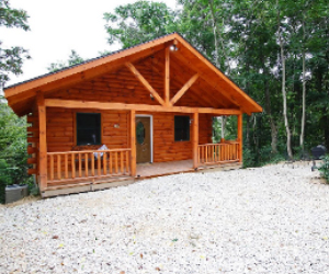 log cabin with front seating area on porch with wooded lot