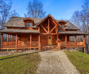 two story log cabin with wrap around porch and gravel driveway
