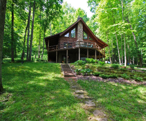 cabin on hill with two story and upstairs deck overlooking the wooded area