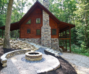 log cabin in woods, Firepit with side view of cabins stone fireplace