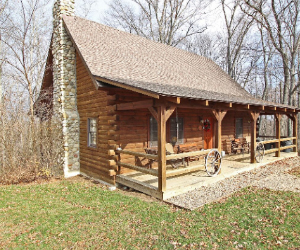 log cabin with long front porch with fence