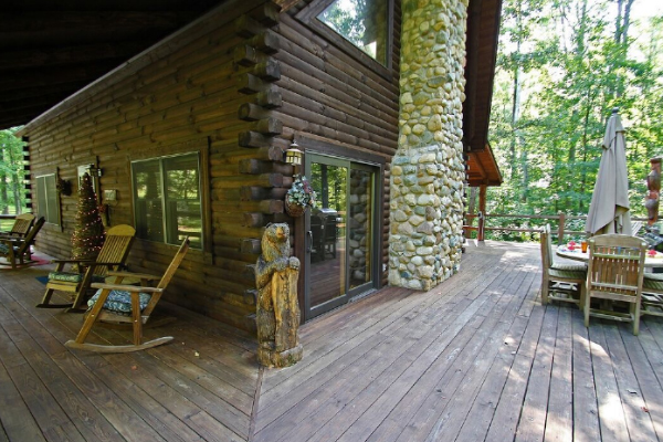 corner of cabin, tall exposed chimeny view, outdoor table area