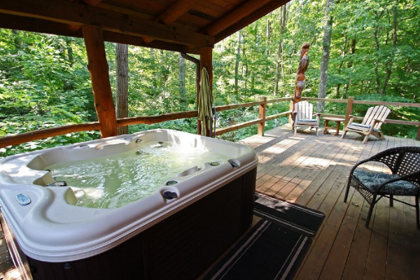 jacuzzi and chairs around area, wooded view