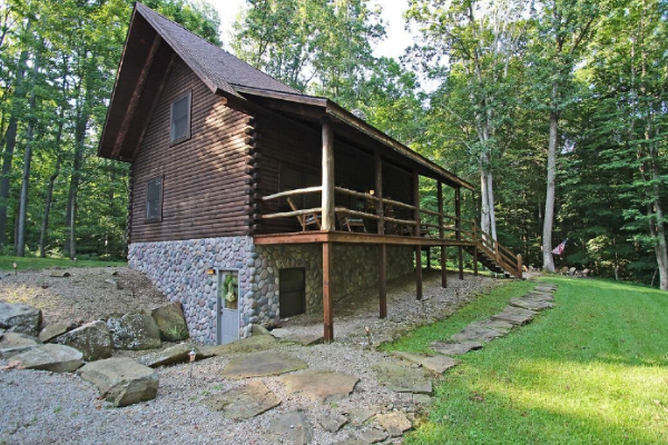 side view of cabin with deck view, stone path walkway
