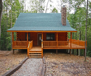 log cabin with green roof and front and side wrap deck and porch area on a wooded area