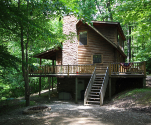 cabin side view on hill with tall stone exterior fireplace and wrap around deck