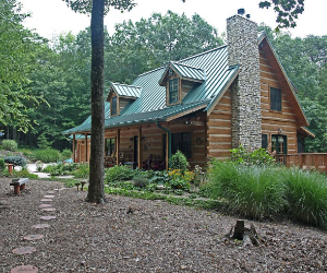 side view of two story lodge with metal green roof and stone fireplace exterior