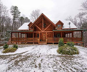 huge lodge with two story view of window of room on top and total wrap around deck and covered deck on the side