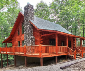 large cabin with wrap around deck and stone fireplace exterior
