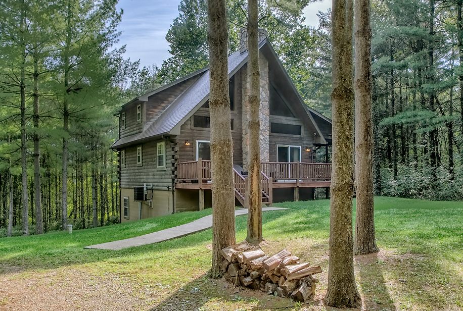 tall trees, cabin with wrap around deck