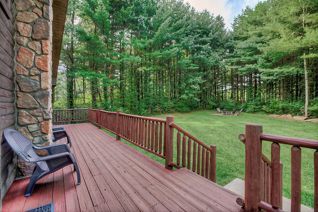 deck, opens to green grass, tall trees, firepit