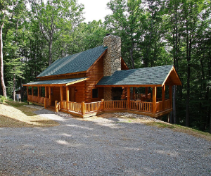 log cabin set back from road with wrap around porch and a green roof with stone fireplace