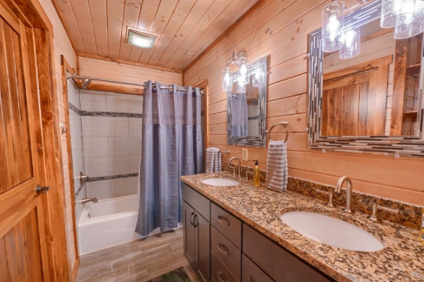 bathroom from access from lower level bedroom with double vanity and tub/shower combo