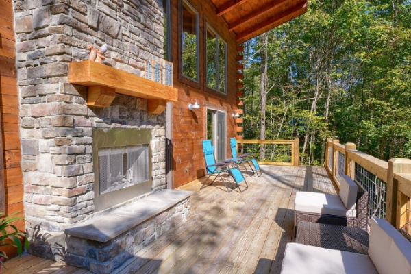 back deck with outdoor wood burning fire place and seating